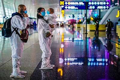 Image: Travelers in protective suits are seen at Wuhan Tianhe International Airport in Wuhan